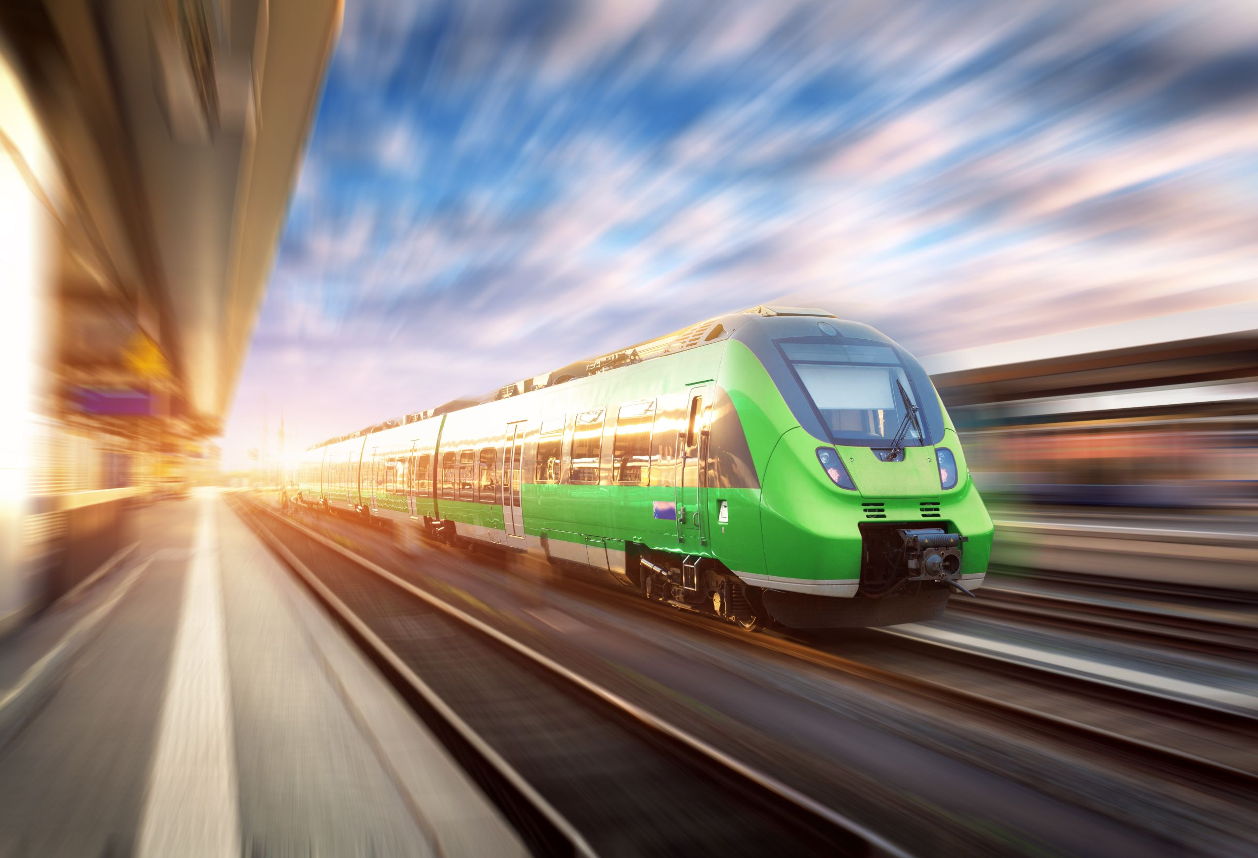Image of a Speedy Green Train going though a railway station with a motion blur background