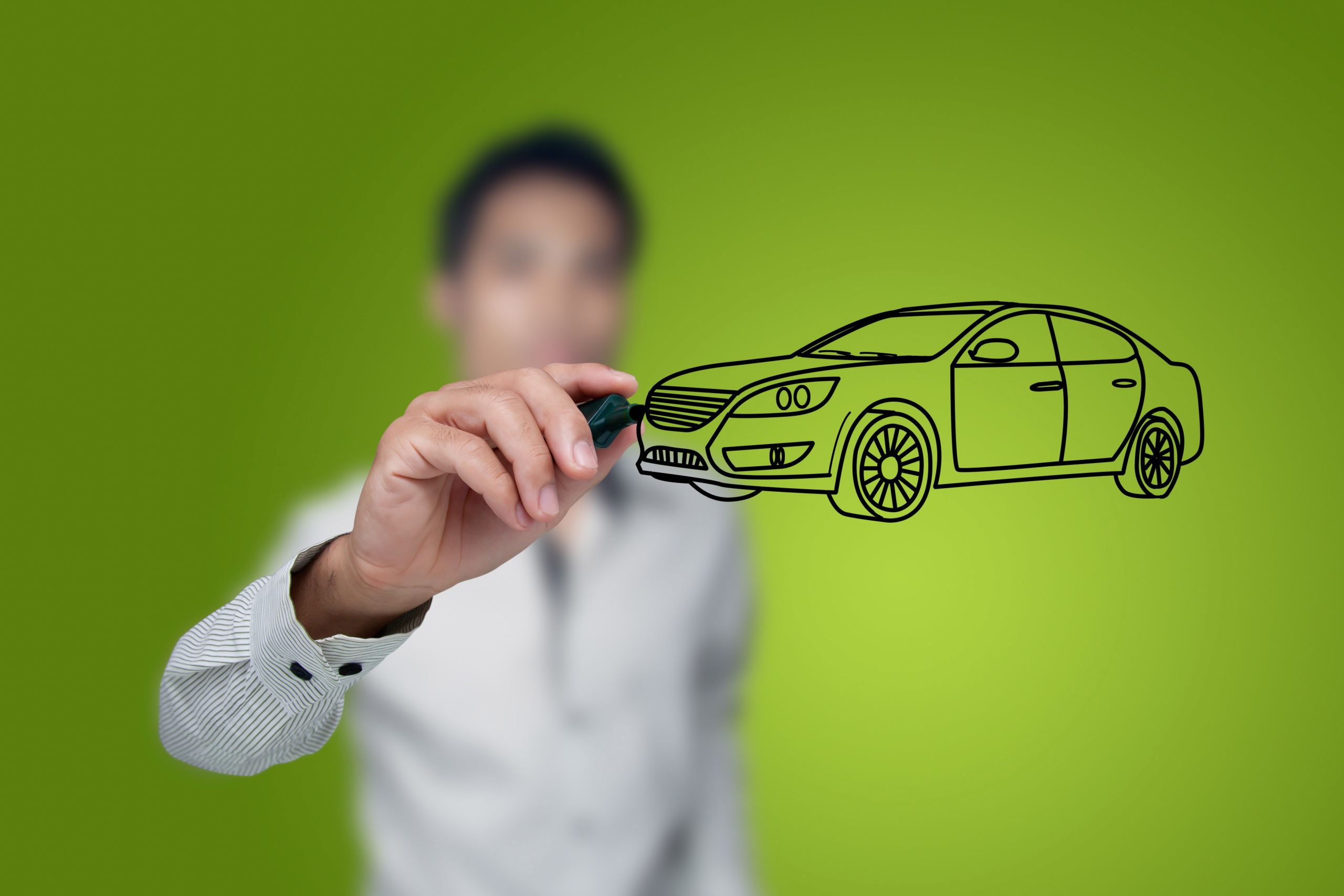 Image of a man drawing an outline of a black car on glass with green background